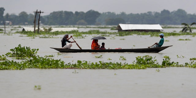 A family travels in a country boat over floodwaters in Gagolmari village, in Morigaon district of Assam, India, July 14.