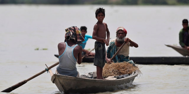 Indian flood affected people row country boats in Gagolmari village, Morigaon district, Assam, India, July 14.