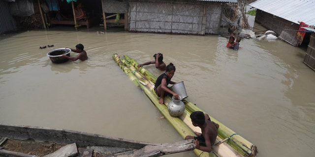 Flood affected villagers are seen near their partially submerged houses in Gagolmari village, Morigaon district, Assam, India, July 14.