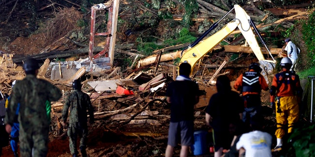People watch a search operation at the site of a mudslide in Ashikita town, Kumamoto prefecture, southwestern Japan, Saturday, July 4, 2020.