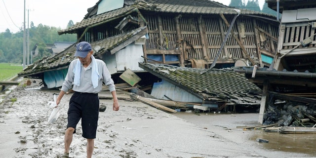 A man walks on muddy road past houses damaged by flood in Kuma village, Kumamoto prefecture, southwestern Japan, Sunday, July 5, 2020.