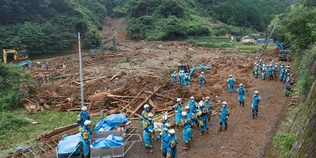 Rescuers search missing people at the site of a mudslide caused by heavy rain in Natsugi town, Kumamoto prefecture, southwestern Japan, Sunday, July 5, 2020.