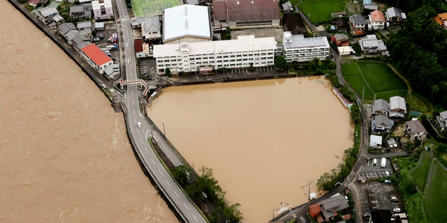 A schoolyard of a junior high school is seen flooded following heavy rains in Gero, Gifu prefecture, central Japan Wednesday, July 8, 2020.