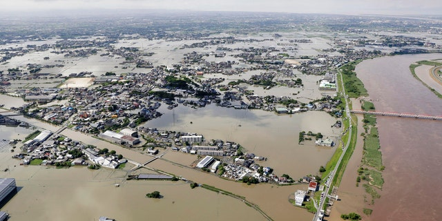 This aerial photo shows the flooded area near the swollen Chikugo River, right, in Kurume city, Fukuoka prefecture, southern Japan Wednesday, July 8, 2020.