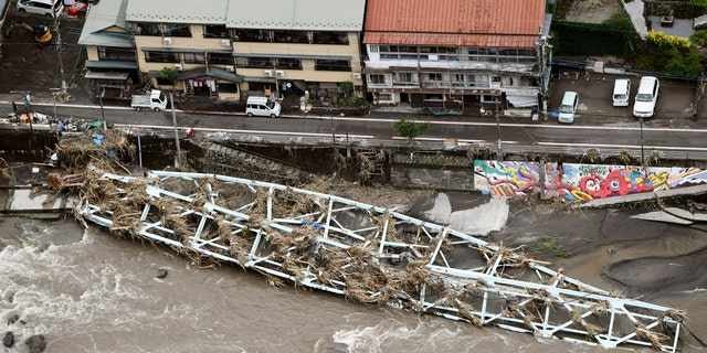 This aerial photo show a damaged bridge lies on the swollen Kusu River after heavy rains in Hita, Oita prefecture, southern Japan Wednesday, July 8, 2020.