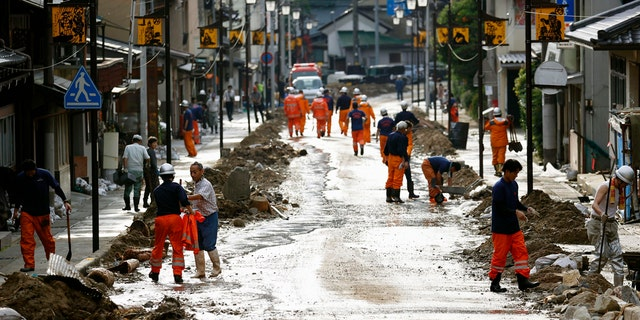 Residents and firefighters put away debris carried by the floodwater in Gero, Gifu prefecture, central Japan Wednesday, July 8, 2020.