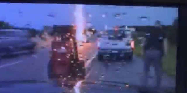 Lightning can be seen striking nearby as an Oklahoma Highway Patrol trooper assists a motorist.