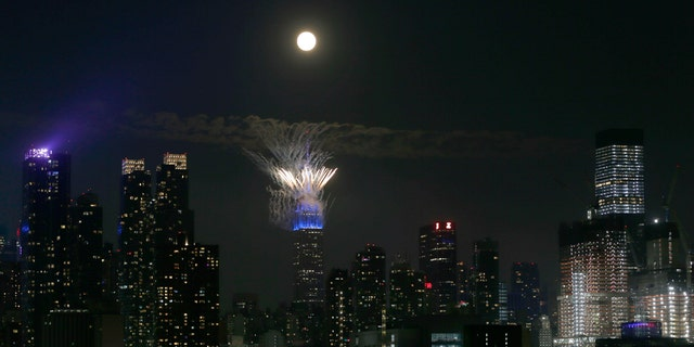 Macy's fireworks go off on the top of the Empire State Building as the full buck moon rises in the sky on July 4, 2020 as seen from Weehawken, New Jersey. (Photo by Gary Hershorn/FOX News)