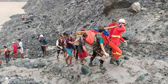 In this photo released from Myanmar Fire Service Department, rescuers carry a recovered body of a victim of a landslide from a jade mining area in Hpakant, Kachine state, northern Myanmar July 2.