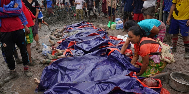 Women look at bodies shrouded in blue and red plastic sheets placed in a row on the ground July 2, in Hpakant, Kachin State, Myanmar.