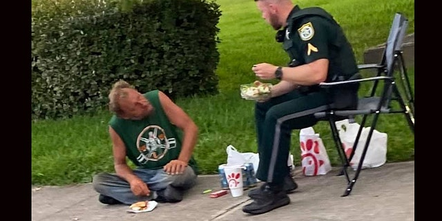 A photo of a Florida sheriff's deputy and homeless man eating Chick-fil-A for lunch together has gone viral on Facebook.