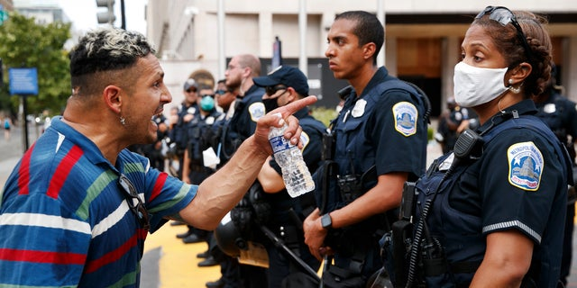 A man yells at a Metropolitan Police officer as demonstrators protest in front of a police line on the section of Washington, D.C., renamed Black Lives Matter Plaza, on June 23. (AP)