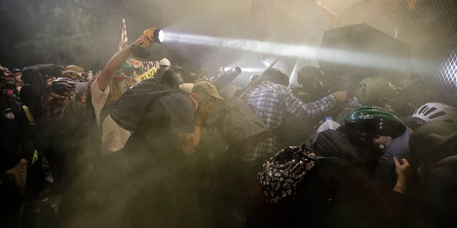 Demonstrators push on a fence as tear gas is deployed during a Black Lives Matter protest at the Mark O. Hatfield United States Courthouse on Saturday in Portland, Ore. (AP Photo/Marcio Jose Sanchez)