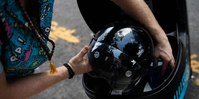 A commuter places a helmet back in the storage compartment of a Revel Transit Inc. electric ride share moped in the Williamsburg neighborhood of the Brooklyn borough of New York. (Photographer: Mark Kauzlarich/Bloomberg via Getty Images)