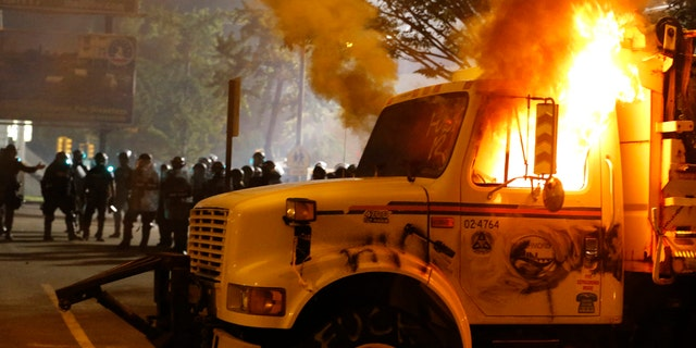 Police stand in front of a utility vehicle that was set on fire by protesters during a demonstration outside the Richmond Police Department headquarters on Grace Street in Richmond, Va., Saturday, July 25, 2020. Police deployed flash-bangs and pepper spray to disperse the crowd after the city utility vehicle was set on fire.