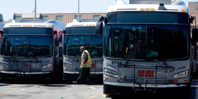 In this April 7, 2020, file photo, a Muni worker walks in front of buses at a San Francisco Municipal Transportation Agency yard in San Francisco. (AP Photo/Jeff Chiu, File)