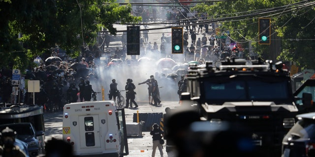Smoke rises as police clash with protesters during a Black Lives Matter demonstration near the Seattle Police East Precinct headquarters on Saturday. (AP)