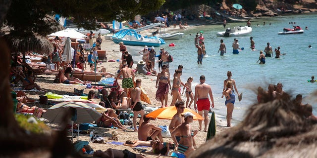 Sunbathers enjoy the beach in Pollença, in the Balearic Island of Mallorca, Spain on Tuesday. The U.K. government's recommendation against all but essential travel to the whole of Spain means that all travelers arriving in Britain from that country will have to undergo a 14-day quarantine. (AP Photo/Joan Mateu)