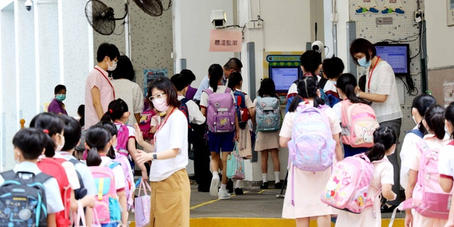 Students wearing face masks wait in line to have body temperatures checked at entrance of a school on June 15, 2020 in Hong Kong, China.
