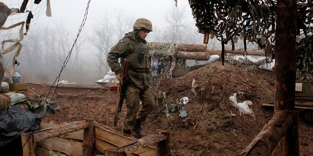 In this file photo dated Monday, Dec. 9 2019, a Ukrainian soldier takes position on the front line at the town of Novoluhanske in the Donetsk region, Ukraine.