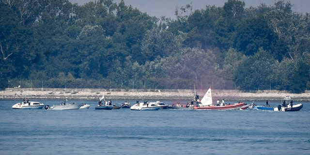 Environmentalists in small boats near the test site of a trial run of the anti-flood system wave protest banners as police speed boats head their way. (AP/LaPresse)