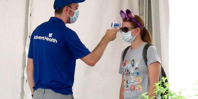 A guests gets her temperature taken before entering the official reopening day of the Magic Kingdom at Walt Disney World in Lake Buena Vista, Fla., July 11. Disney reopened two Florida parks, the Magic Kingdom and Animal Kingdom, Saturday with limited capacity and safety protocols in place. (Joe Burbank/Orlando Sentinel via AP)