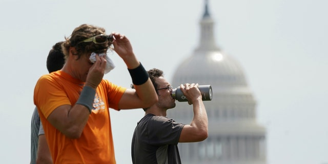 With the U.S. Capitol in the background, players cool off after a game of ultimate frisbee on the National Mall during a heat wave in Washington, U.S., July 20, 2020.