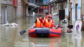 Heavy rains, floods in China strand dozens on rooftops, triggering landslides