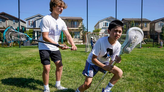 2 teen lacrosse players score goal in fight against hunger