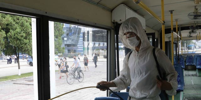 A man in a protective suit disinfects the inside of a wheelchair bus to help curb the spread of coronavirus in Pyongyang, North Korea, on Thursday, August 13, 2020. (AP Photo / Jon Chol Jin)