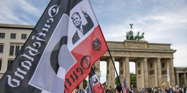 A protestor holds a flag of the German Reich with a picture of US President Donald Trump in front of the Brandenburg Gate before a demonstration against the coronavirus measures by the German Government in Berlin, Germany, Saturday, Aug. 29, 2020 - file photo.