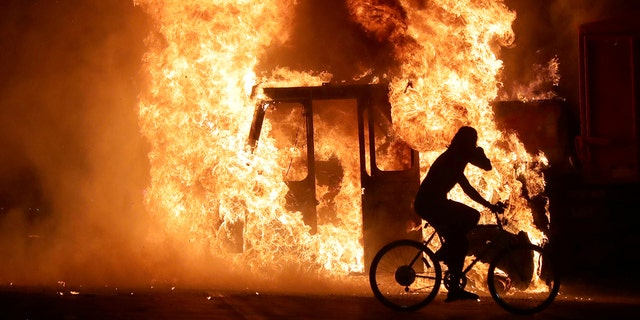A man on a bike rides past a city truck on fire outside the Kenosha County Courthouse in Kenosha, Wisconsin, U.S., during protests following the police shooting of Black man Jacob Blake August 23, 2020. Picture taken August 23, 2020. Mike De Sisti/Milwaukee Journal Sentinel via USA TODAY via REUTERS.