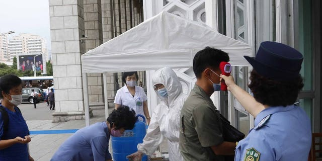 People disinfect their hands and take their temperatures before going to Pyongyang Railway Station in Pyongyang, North Korea, on Thursday, August 13, 2020. (AP Photo / Cha Song Ho)