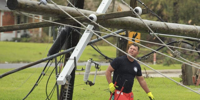 A fireman looks for a place to cut fallen power lines, Friday, Aug. 28, 2020, in Westlake, La., as cleanup efforts continue following Hurricane Laura moved through the area.