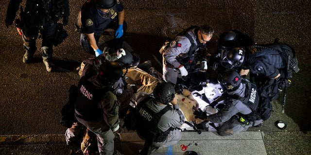 A man is treated after being shot Aug. 29, 2020, in Portland, Ore. It wasn't clear if the fatal shooting was linked to fights that broke out as a caravan of about 600 vehicles was confronted by counterdemonstrators in the city's downtown. (AP Photo/Paula Bronstein)