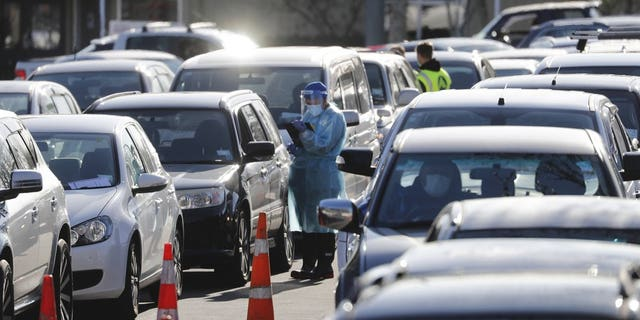Cars queue at a COVID-19 test centre in Auckland, New Zealand, Thursday, Aug. 13. Health authorities in New Zealand are scrambling to trace the source of a new outbreak of the coronavirus as the nation's largest city goes back into lockdown. (AP Photo/Dean Purcel)