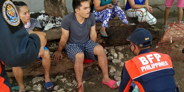 An injured man is treated after a strong earthquake struck in Cataingan, Masbate province, central Philippines on Tuesday Aug. 18, 2020.