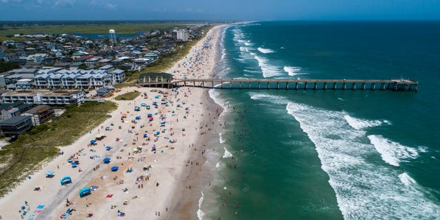 Beachgoers pack Wrightsville Beach, NC, on Sunday, August 2, 2020 as Land Isaias Storm moves along the Southeast Coast.  (Travis Long / News & Observer through AP)