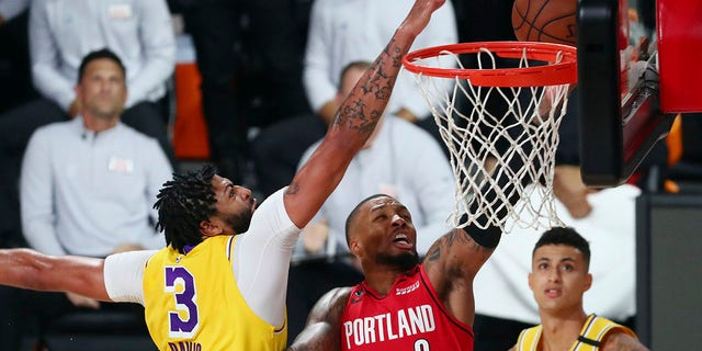 Los Angeles Lakers forward Anthony Davis (3) blocks a shot by Portland Trail Blazers guard Damian Lillard (0) as Lakers forward Kyle Kuzma (0) looks on during the first half of Game 2 of an NBA basketball first-round playoff series, Thursday, Aug. 20, 2020, in Lake Buena Vista, Fla. (Kim Klement/Pool Photo via AP)