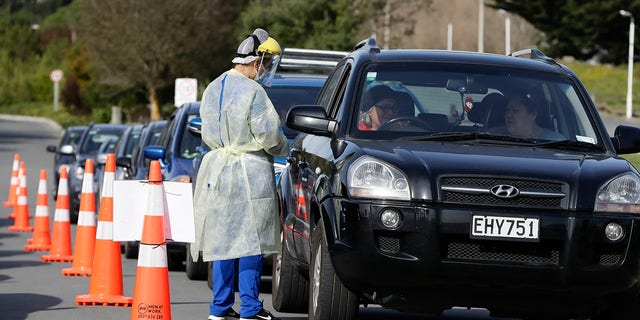 Métis - Medical staff prepare to take a COVID-19 test from a visitor to a drive-through community-based assessment center in Christchurch, New Zealand, on Aug. 13, 2020. (AP Photo/Mark Baker)