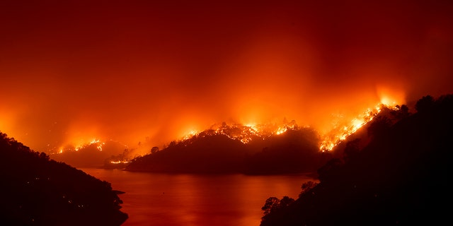 Flames from the LNU Lightning Complex fires burn around Lake Berryessa in unincorporated Napa County, Calif., on Wednesday, Aug. 19, 2020.