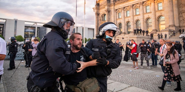 Police officers push away a crowd of demonstrators from the square 'Platz der Republik' in front of the Reichstag building during a demonstration against the Corona measures in Berlin, Germany, Saturday, Aug. 29, 2020. (Christoph Soeder/dpa via AP)
