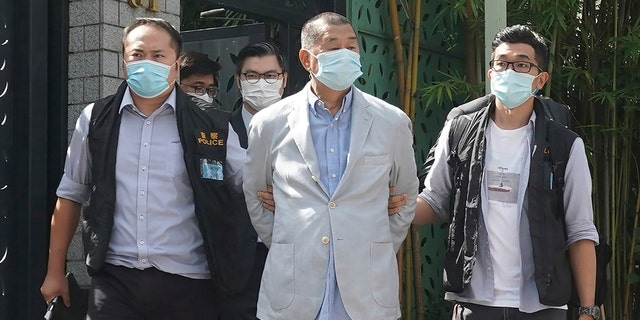 Hong Kong media tycoon Jimmy Lai, center, who founded local newspaper Apple Daily, is arrested by police officers at his home in Hong Kong, Monday, Aug. 10, 2020. (AP Photo)