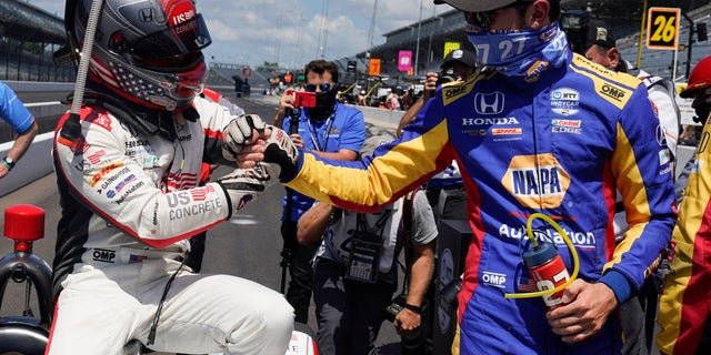 Rossi, wearing blue, congratulates teammate Marco Andretti for winning the Indy 500 pole.