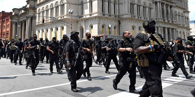 "Armed members of the ""NFAC"" march through downtown Louisville, Ky., toward the Hall of Justice on Saturday, July 25, 2020.  (AP Photo/Timothy D. Easley)"