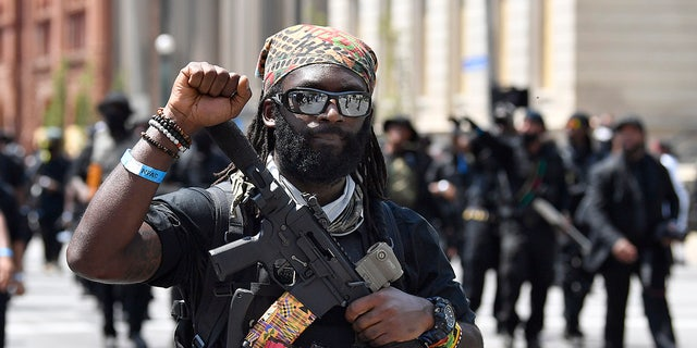 "An armed member of the ""NFAC"" raises his fist during a march through downtown Louisville, Ky., toward the Hall of Justice on Saturday, July 25, 2020.  (AP Photo/Timothy D. Easley)"