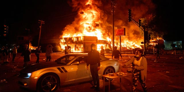 An AutoZone store burns as protesters gather outside of the Third Precinct in Minneapolis Thursday, May 28, 2020. (Mark Vancleave/Star Tribune via AP)