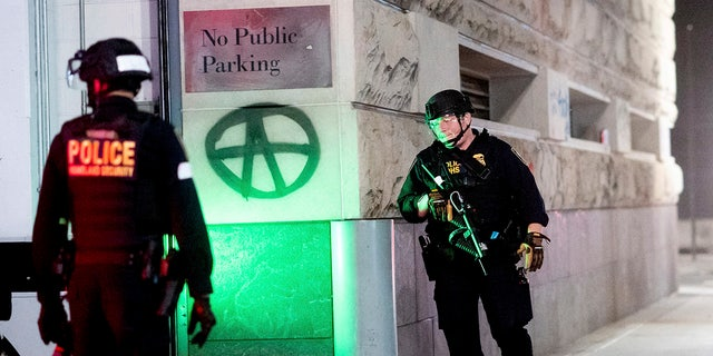 Department of Homeland Security officers guard a back entrance to the Mark O. Hatfield U.S. Courthouse on Saturday, Aug. 1, 2020, in Portland, Ore.  (AP Photo/Noah Berger)