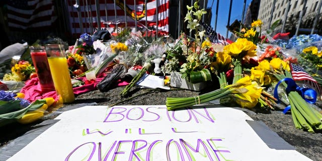 FILE - In this April 17, 2013 photograph, flowers and signs adorn a barrier, two days after two explosions killed three and injured hundreds, at Boylston Street near the of finish line of the Boston Marathon at a makeshift memorial for victims and survivors of the bombing. A federal appeals court has overturned the death sentence of Dzhokhar Tsarnaev in the 2013 Boston Marathon bombing, Friday, July 31, 2020, saying the judge who oversaw the case didn't adequately screen jurors for potential biases. (AP Photo/Charles Krupa, File)