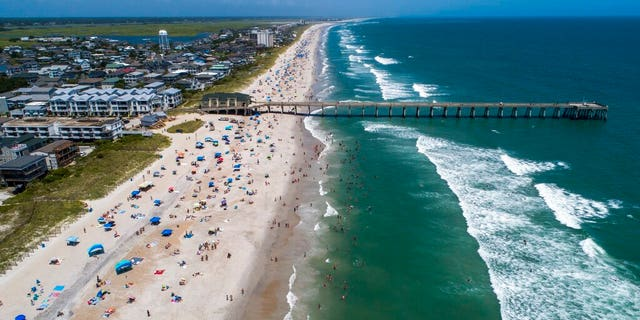 Beachgoers pack Wrightsville Beach, N.C., Aug. 2, as Tropical Storm Isaias moves along the Southeast Coast. (Travis Long/The News & Observer via AP)
